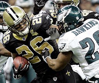 Saints RB Deuce McAllister fends off Eagles DB Brian Dawkins.